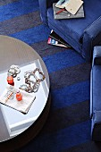 Coffee table and blue armchair on striped carpet