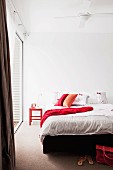 Bedroom - white bed linen and red scatter cushion on double bed in minimalist ambiance