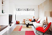 Designer living room with red, upholstered rocking chair next to woman sitting on couch and dog below window
