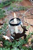 Marmeladenglas mit Kerze und Hirschplätzchen zu Weihnachten
