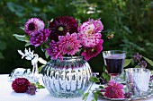 Pink dahlias in spherical, silver vase next to glass of red wine on silver tray in garden