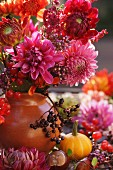 Bouquet of red dahlias with sprig of berries in vase