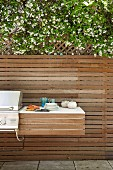Shelf next to barbecue mounted on modern wooden fence of terrace