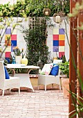 White, rattan outdoor furniture on terrace with terracotta floor and colourful tiles on courtyard wall