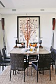 Oars and pictures of shells and starfish in large frame as maritime decor behind large dining table with stone top and dark chairs with leather seats