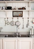 Twin sinks with white base cabinet below kitchen utensils hanging from hooks under wooden, wall-mounted shelf