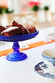Pieces of chocolate cake on blue glass cake stand