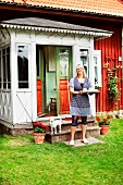 Smiling woman holding tray outside porch of Swedish wooden house