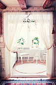 Seating area with white period furniture in decorated window bay with draped curtains and mistletoe hung in entrance