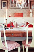 Nostalgic dining area with lit candles and bowl of winter apples on dining table
