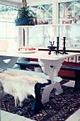 Essplatz in skandinavischer Landhausromantik mit rustikalem Esstisch und Fell auf einer Sitzbank