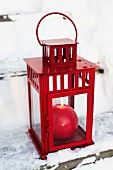 Red, spherical candles in red lantern on snowy wooden steps