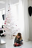 Girl playing with toy car on white wooden floor in front of white, artificial Christmas tree with purple baubles