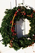 Advent wreath with red berries hanging on exterior door