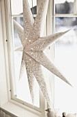 White paper star lantern with delicate pattern of circles hanging from window frame