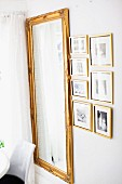 Gilt-framed photos next to ornate, antique mirror
