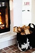 Logs in animal-skin bag next to fire in masonry fireplace
