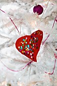 Red, hand-crafted love heart with colourful sequins and purple bauble on white, artificial Christmas tree