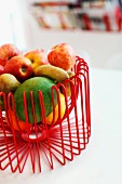 Fruit in bowl made of red, curved wire