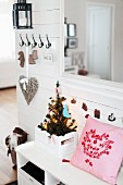 Pink cushion next to small, decorated Christmas tree in crate on white cloakroom bench in rustic hallway