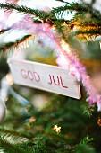 Holzschildchen mit Weihnachtsgruss an Tannenzweig hängend