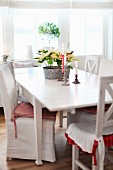 Chairs with white loose cover and kitchen chairs around lit candles & potted plant on table