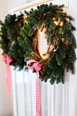 Christmas wreaths of fir branches and ribbons hanging on cupboard door