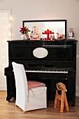 Strohfigur auf Boden neben Stuhl mit weisser Husse vor schwarzem Klavier