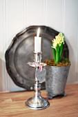 Brennende Kerze in Silber-Kerzenständer, im Hintergrund Hyazinthe im Topf und Zinkteller an Wand
