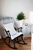 Black-painted wooden rocking chair with white cushion next to water jug of fir branches on side table