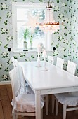 Dining table and chairs painted white below traditional chandelier with glass pendants in rustic dining area with pastel floral wallpaper and festive star ornaments in windows