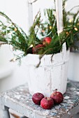 Red apples in front of whitewashed bucket of branches with festive decorations on vintage stool