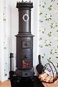 Vintage, cylindrical wood-burning stove and basket of firewood in corner of room with romantic floral wallpaper