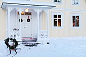 Festively decorated sledges in snowy front garden on pale yellow Swedish house with roofed porch