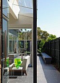 Glass walls create seamless transition between seating area in interior and narrow courtyard with stone bench against screen fence; decorative glass vase