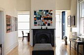 Modern artwork above central open fireplace flanked by open doorways with further artworks and console table; ottoman in foreground
