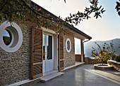 Mediterranes Wohnhaus mit Bullaugenfenster und Terrassentür mit Türläden aus Holzlamellen