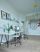 Long desk and two swivel chairs in room with wooden board floor