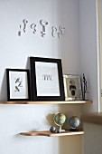 Collection of globes and framed pictures on wooden, wall-mounted shelves below ornamental keys on wall