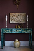 Elegant, silver candlesticks on vintage-style console table with drawers below antique low-relief on aubergine-coloured wall