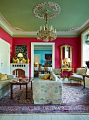 Grand salon with deep pink walls, pastel green stucco ceiling, chandelier above seating area and view of dining table through open doorway in background