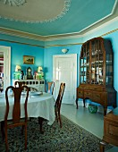 Grand dining room painted light blue with set table opposite display cabinet
