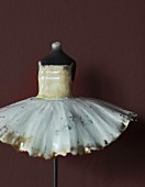 Painted, china torso wearing tutu on metal stand
