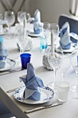 Festively set table with white and blue linen napkins on plates and various wine glasses