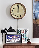 Old station clock above black, extending, retro wall lamp and framed posters on sideboard