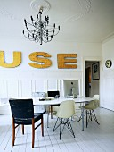 Modern table and classic chairs on white wooden floor in grand, period apartment with gilt decorative letters on wall