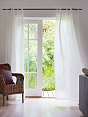 Rattan armchair next to lattice window with airy, white curtains and garden view