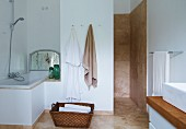 Laundry basket on floor between fitted bathtub in niche and shower area with beige, marbled tiles on walls and floor
