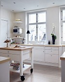 Island counter with drawers on castors in white, country-house kitchen with recessed spotlights in suspended ceiling
