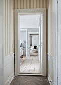 View from narrow hallway with striped wallpaper and herringbone parquet into living area with rustic wooden floor